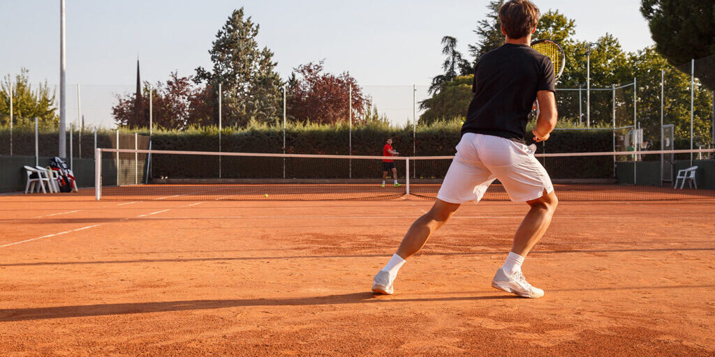 Professional tennis player playing tennis on a clay tennis court