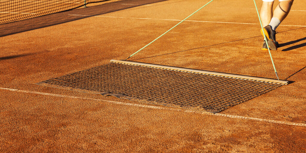 Preparing a tennis court for the match. Man aligns ground cover.