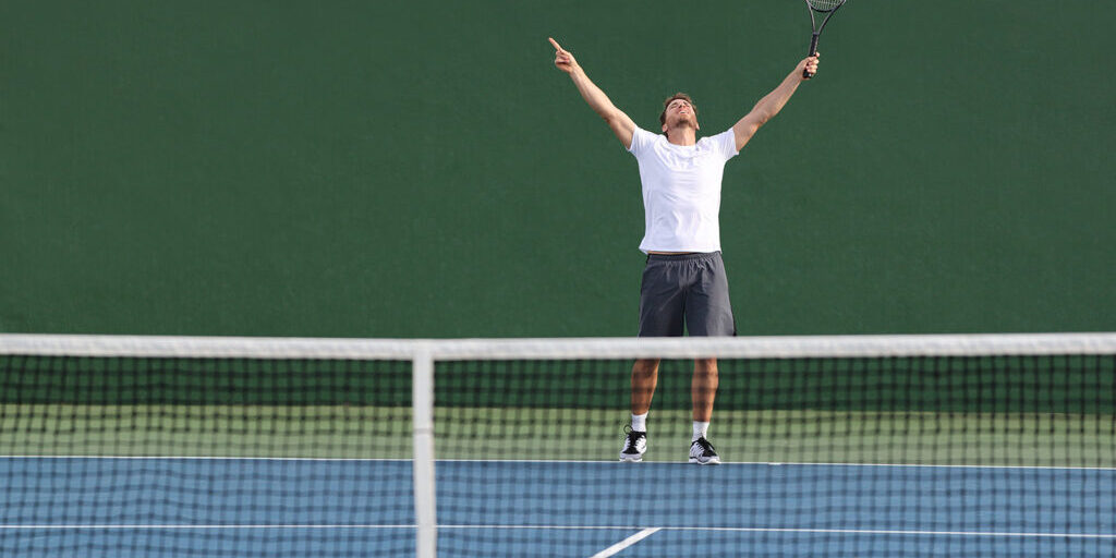 Tennis player man winning match happy excited with arms up in success on green outdoor court.